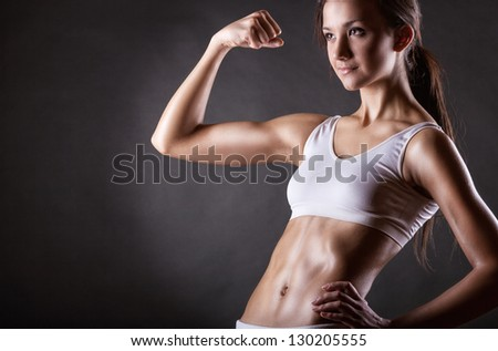 Attractive athletic girl showing biceps on a dark background - stock photo