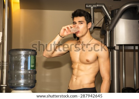 Attractive athletic shirtless young man drinking water from dispenser in gym while looking at camera - stock photo