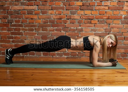 Attractive athletic woman in black top and leggins performing plank exercise - stock photo