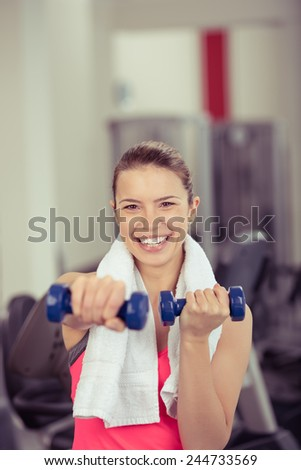 Attractive athletic woman lifting weights working out in a gym with dumbbells looking at the camera with a beaming friendly smile, with copyspace above - stock photo