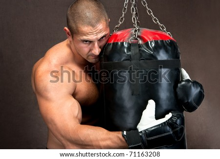 Attractive athletic young man training kickboxing using black punching bag - stock photo