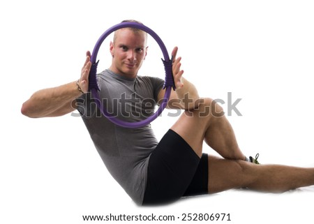 Attractive athletic young man working out with pilates ring on white background, looking at camera - stock photo