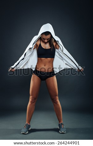 Attractive athletic young woman posing in studio on dark background - stock photo
