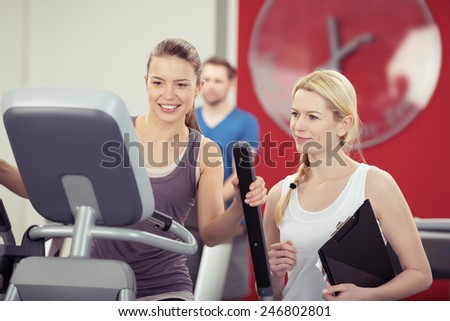 Attractive athletic young woman training with a female personal trainer in a gym checking her performance on the equipment with a smile - stock photo