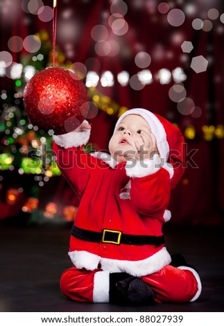 Attractive baby catching the huge Christmas ball - stock photo