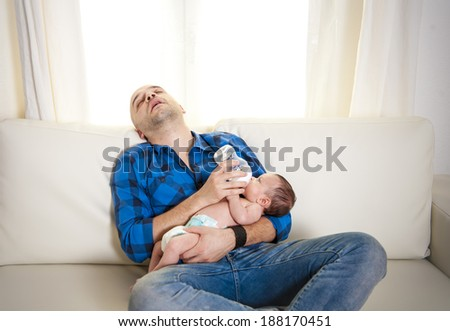 attractive bald latin new father exhausted , tired and asleep while feeding his newborn baby boy with milk bottle sitting on a white couch in living room at home - stock photo
