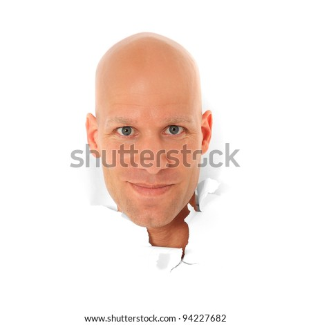 Attractive bald man breaks his head trough white paper wall. All on white background. - stock photo