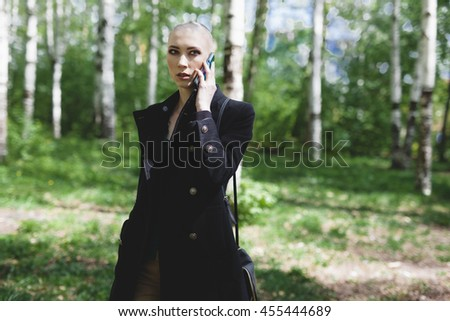 Attractive bald sexy woman walking in forest with phone. Outdoors lifestyle portrait of pretty girl