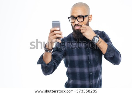 Attractive baldheaded african american man in glasses touching moustache and taking selfie - stock photo