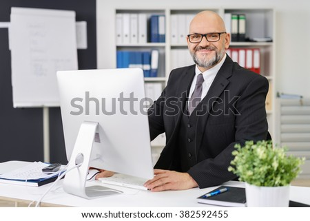 Attractive balding businessman working at his desk in the office on a desktop computer looking across at the camera with a friendly smile - stock photo