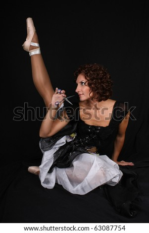 attractive ballerina with scissors sitting over black background