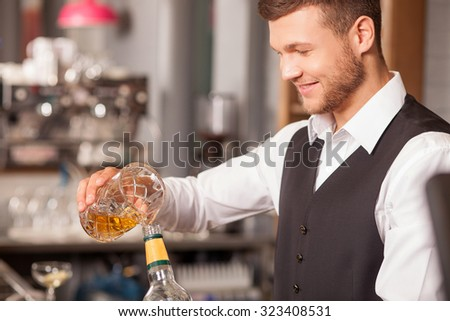 Attractive barman is pouring mixed drink into bottle. He is looking at self-made beverage and smiling. The man is standing in bar - stock photo