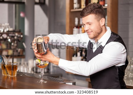 Attractive bartender is creating beverage with inspiration. He is pouring mixed drink from shaker into glass. The man is looking at beverage happily and smiling - stock photo