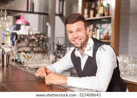 Attractive bartender is standing and leaning on counter is pub. He is looking forward with joy. The man is uniform is smiling - stock photo
