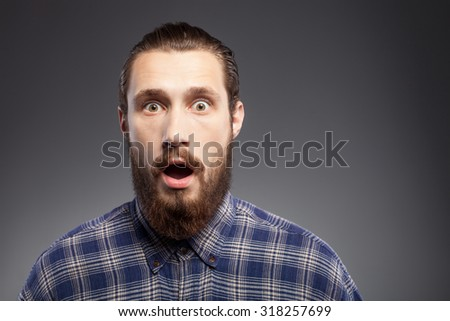 Attractive bearded guy is standing in blue shirt. He is looking at the camera with shock. His mouth and eyes are wide open. Isolated on black background and copy space in right side - stock photo