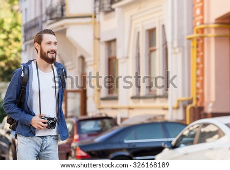 Attractive bearded male tourist is making journey across city. He is standing with backpack and smiling. The guy is looking around and holding camera. Copy space in right side - stock photo
