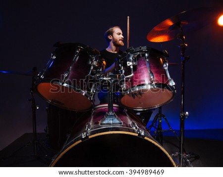 Attractive bearded man drummer sitting and playing on his kit over dark background - stock photo