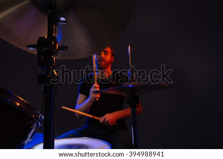 Attractive bearded man drummer with closed eyes enjoying playing drums over dark background - stock photo