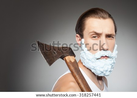 Attractive bearded man is holding an axe. He has shaving foam over his face. The man is looking forward seriously. Isolated on grey background and copy space in left side - stock photo