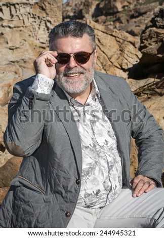 Attractive bearded man on the beach with sunglasses