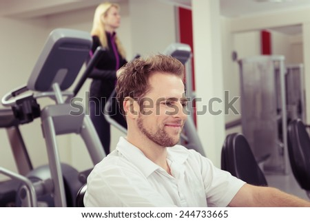Attractive bearded man working out at the gym smiling as he exercises on the equipment, close up head and shoulders view in profile - stock photo