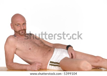 Attractive bearded middle aged man in swimming suit, alternative lifestyle, tattoo and piercing - stock photo