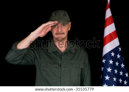 Attractive bearded middle aged man, soldier,  saluting American flag, studio shot, black background. - stock photo