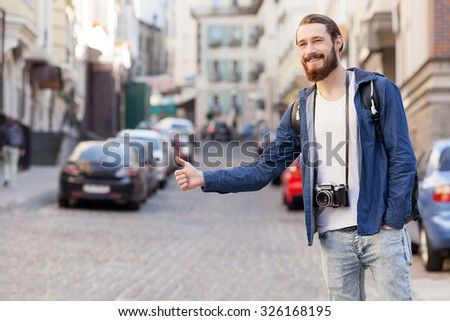 Attractive bearded tourist is hitchhiking in city. He is standing and raising hand sideways. The man is looking forward and smiling. He is carrying backpack and camera - stock photo