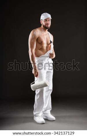 Attractive bearded young painter in white dungarees, hat and bare chest standing with paint roller, on a gray background - stock photo