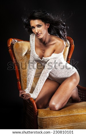 Attractive beautiful brunette woman posing in sexy lingerie, sitting on chair - stock photo