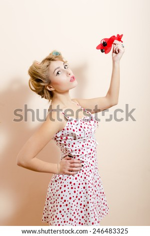 Attractive beautiful funny pinup blond housewife playing with airplane and dreaming about traveling - stock photo