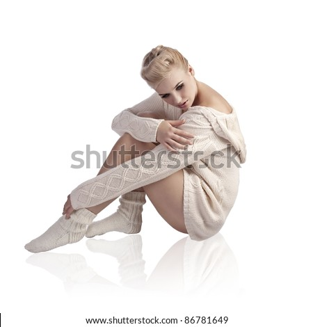attractive beautiful woman wearing a white wool sweater in a fashion shot with elegant hair style - stock photo