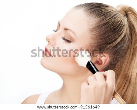 Attractive beautiful young woman applying blusher