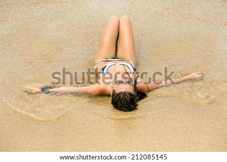 Attractive beautiful young woman in swimsuit lying on the sand near the ocean - stock photo