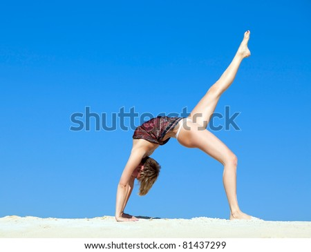 Attractive beautiful young woman in yoga pose against the blue sky