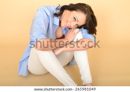 Attractive Beautiful Young Woman Sitting on the Floor Wearing a Blue Shirt and White Jeans Smiling and Looking Up at The Camera - stock photo