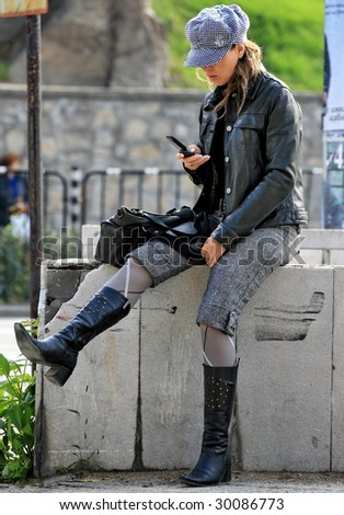attractive beautiful young woman with cap holding cell phone, street behind her