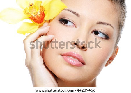 Attractive beauty asian female face with flower from ear - isolated on white - stock photo