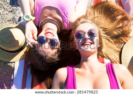 Attractive best friends having fun on the beach,Girls Laughing and having fun on beach.summer holidays and vacation-girls sunbathing on the beach.Summer things and accessorize,trendy bikini,sunglasses - stock photo