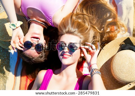 Attractive best friends having fun on the beach in summer.Laughing and having fun.Two young teenage girls looking on camera and sending you air kiss,wear bikini sunglasses and fashion bright jewelry - stock photo