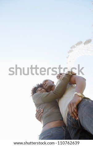 Attractive black couple hugging against a blue sky on vacation while visiting the London Eye.
