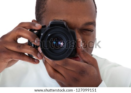 Attractive black guy making a picture with his camera. All on white background.