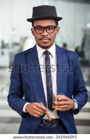 Attractive black man with a cigar and a glass of cognac. - stock photo