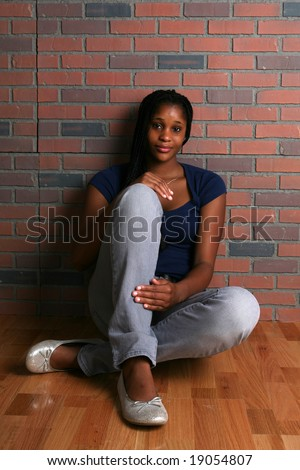 attractive black teenage girl sitting on the floor and leaning against a brick wall