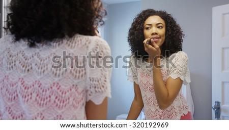 Attractive black woman applying make-up - stock photo