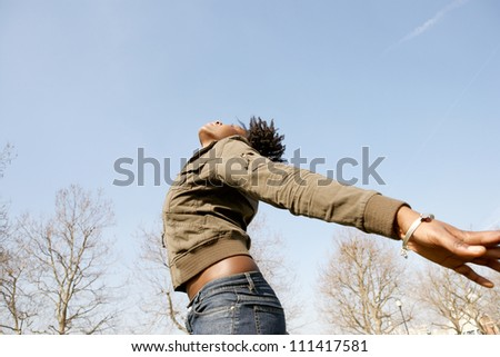 Attractive black woman expressing freedom against an intense blue sky, bending backwards with her arms stretched. - stock photo