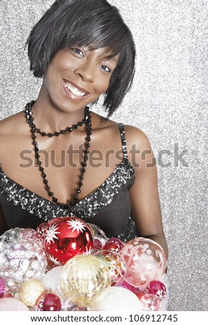 Attractive black woman holding Christmas barballs with a glittering background.