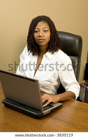 attractive black woman in office working computer braided hair - stock photo