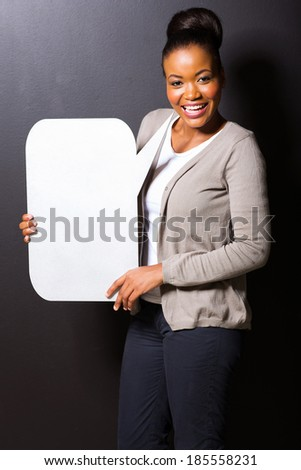 attractive black woman with blank text bubble isolated on black - stock photo