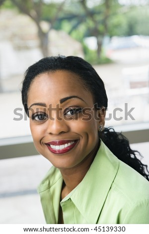 Attractive black woman with pulled back hair sits in front of a window and smiles at the camera. Vertical shot. - stock photo